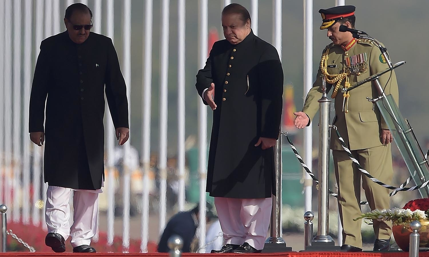 Prime Minister Nawaz Sharif guides President Mamnoon Hussain during a Pakistan Day military parade.─AFP
