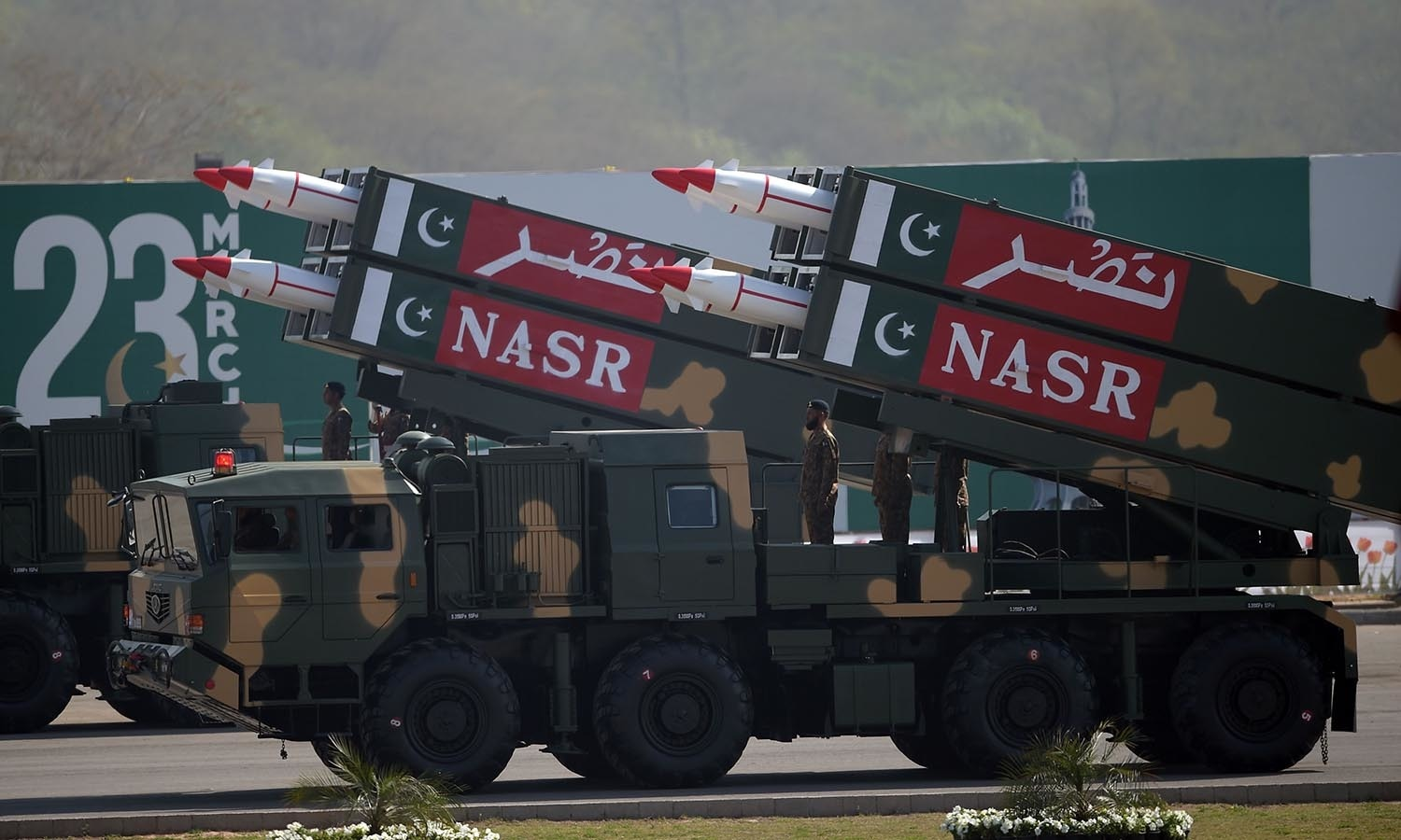 Pakistani military personnel stand beside short-range Surface to Surface Missile NASR during a Pakistan Day military parade─AFP