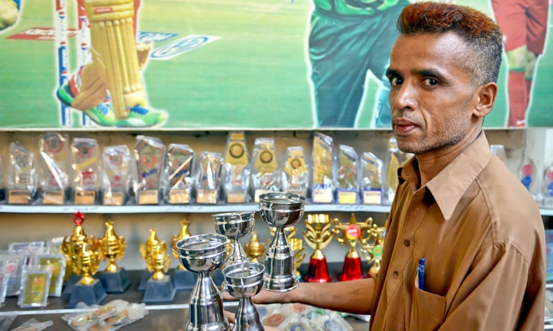 Mohammad Ali lays out Sialkoti trophies on the counter | Photos by Fahim Siddiqi/White Star