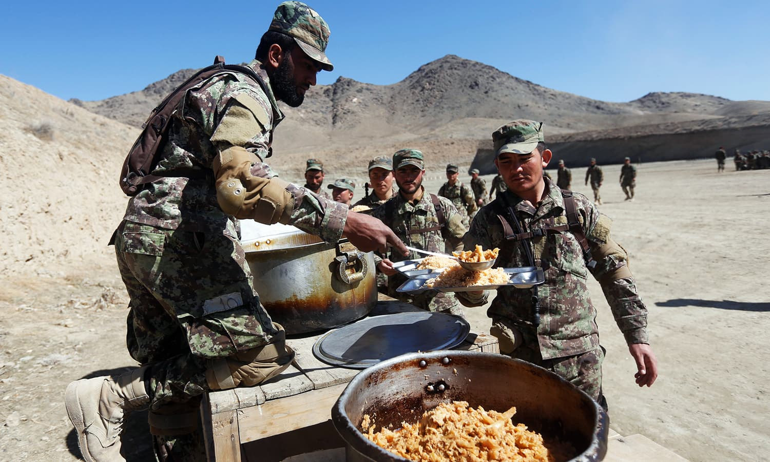 New recruits to the Afghan army Special Forces have their lunch after take part in a military demonstration in Rishkhur. —Reuters