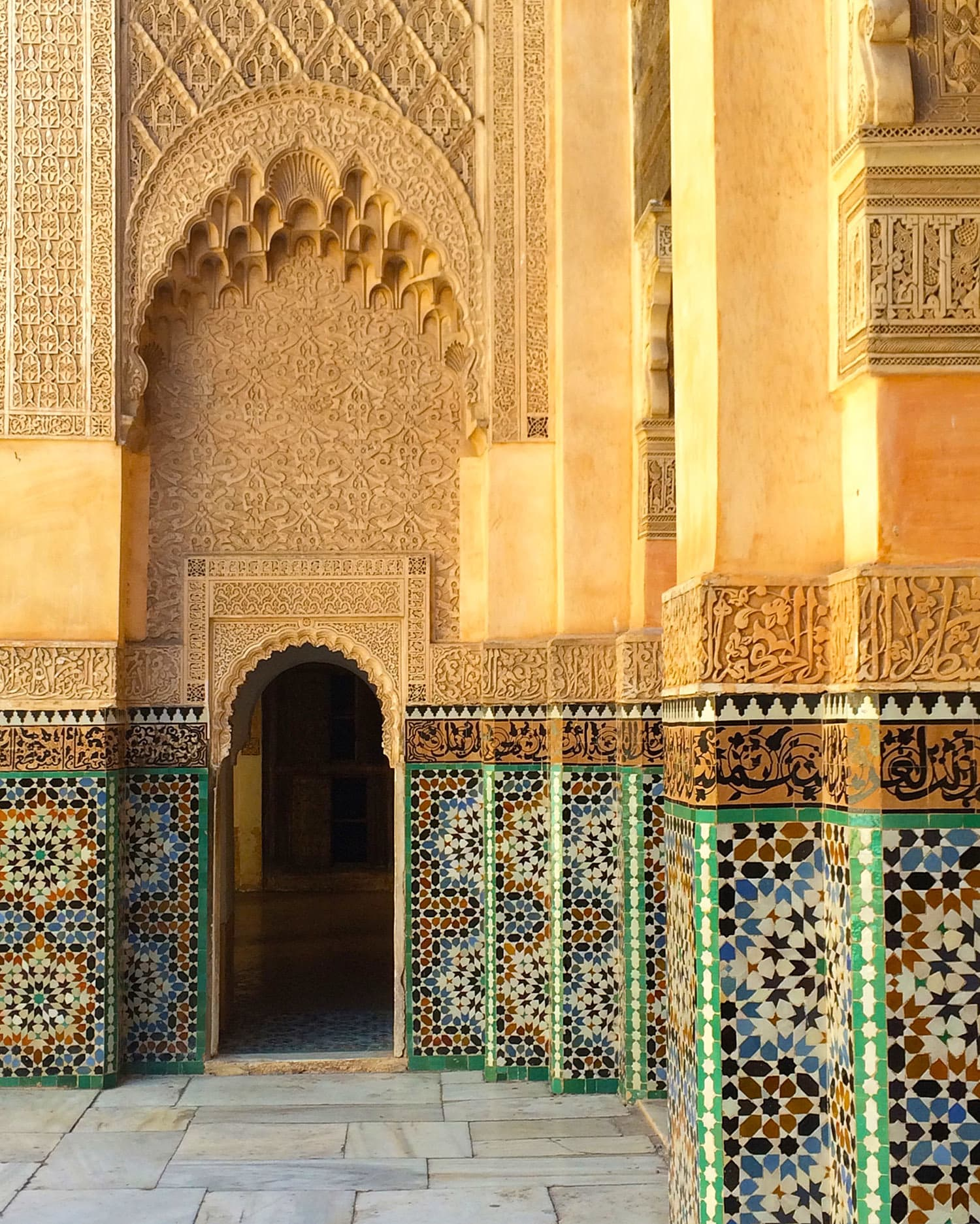 Colourful tiles, Arabic script, and ornate carvings at Medersa Ben Youssef.