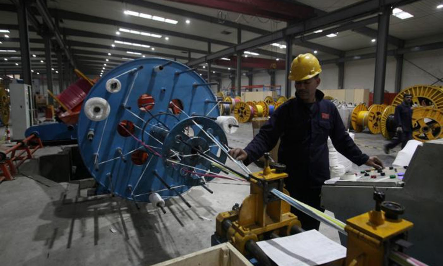 A worker monitors automatic copper wire unit at Pakistan Cables in Karachi.─Reuters