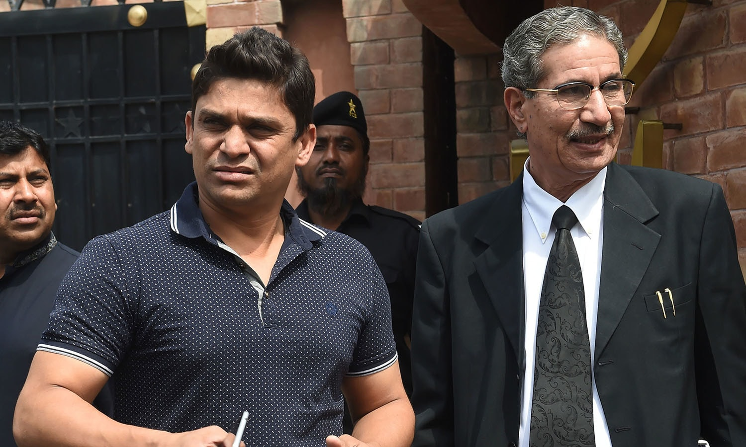 Suspended Pakistani cricketer Khalid Latif (L) leaves with his lawyer after appearing before a tribunal in Lahore.─AFP