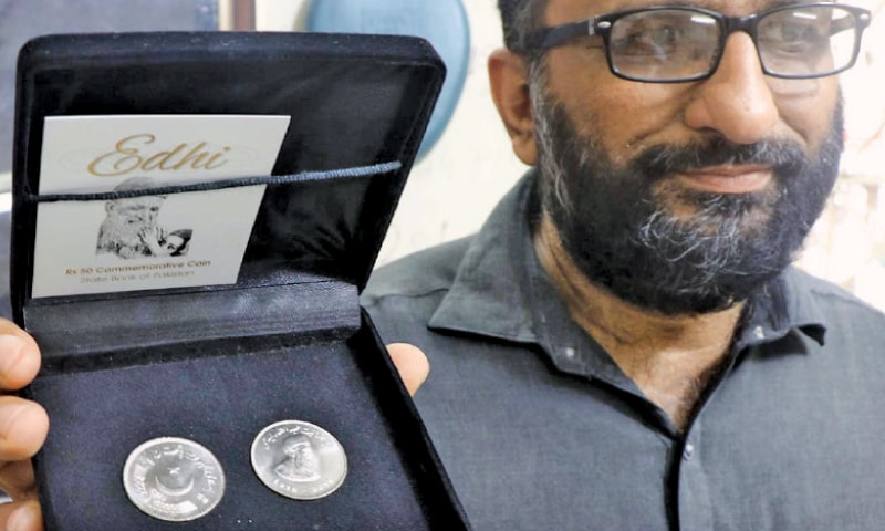 Faisal Edhi, son of late humanitarian Abdul Sattar Edhi, hold s the coin issued in honour of his father.