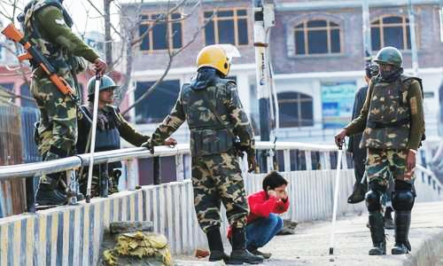 Indian paramilitary soldiers force a Kashmiri child to perform sit-ups.—AP