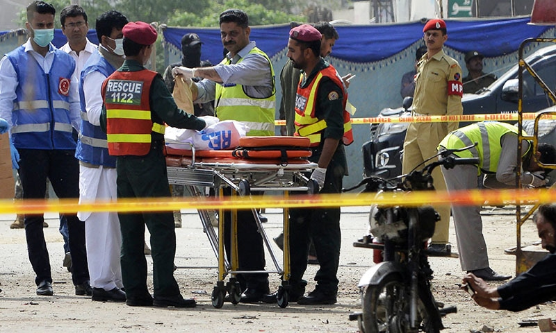 Security officials collect evidence from the scene of a suicide bomb attack in Lahore on April 5.— AFP
