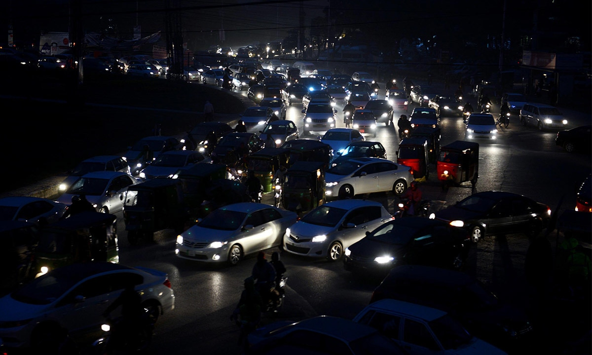 Car headlights light up a busy road in Karachi during load-shedding