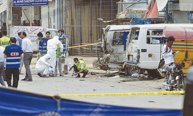 A FORENSIC team inspects the site after a suicide attack on a census team on Bedian Road on Wednesday.—M. Arif / White Star