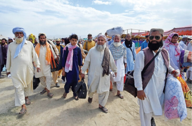People arriving at the venue of Jamiat Ulema-i-Islam's conference in Azakhel, Nowshera, on Thursday. — Photo by Abdul Majeed Goraya