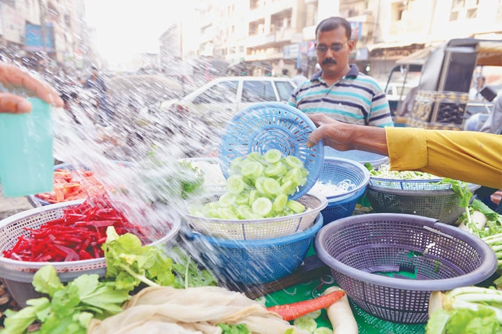 Sprinkling cool water on the vegetables keeps them fresh. -Photos by Fahim Siddiqi / White Star