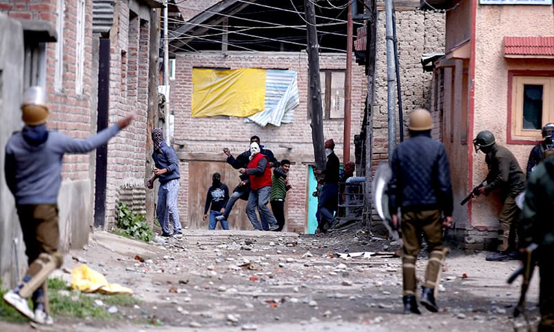Kashmiri demonstrators throw stones towards Indian policemen during a protest against by-polls in Srinagar. ─Reuters