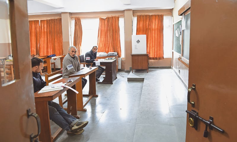 SRINAGAR: Election staff wait for voters at a polling station on Sunday.— AFP