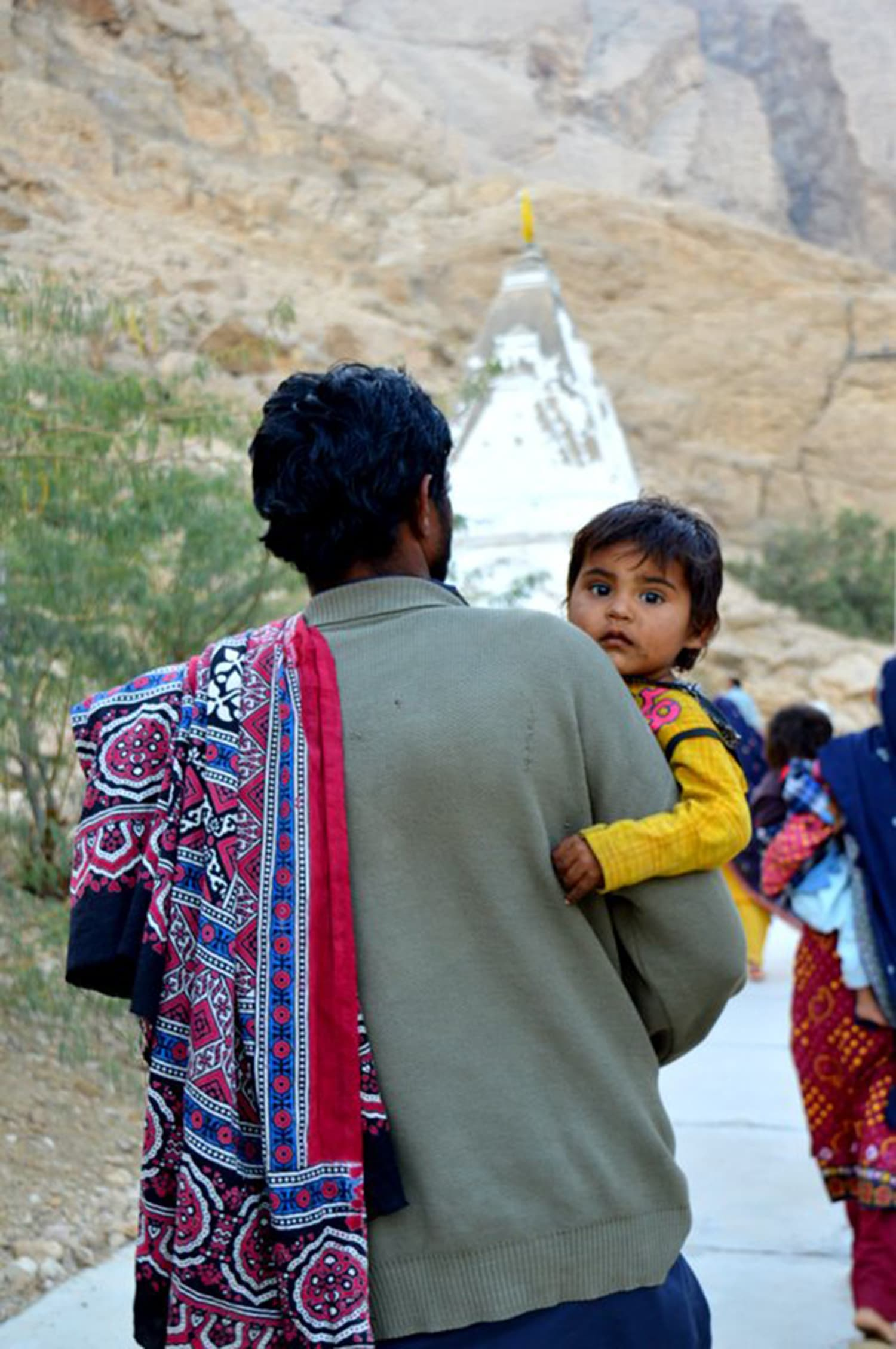 A Balochi man walking to the temple with his child.