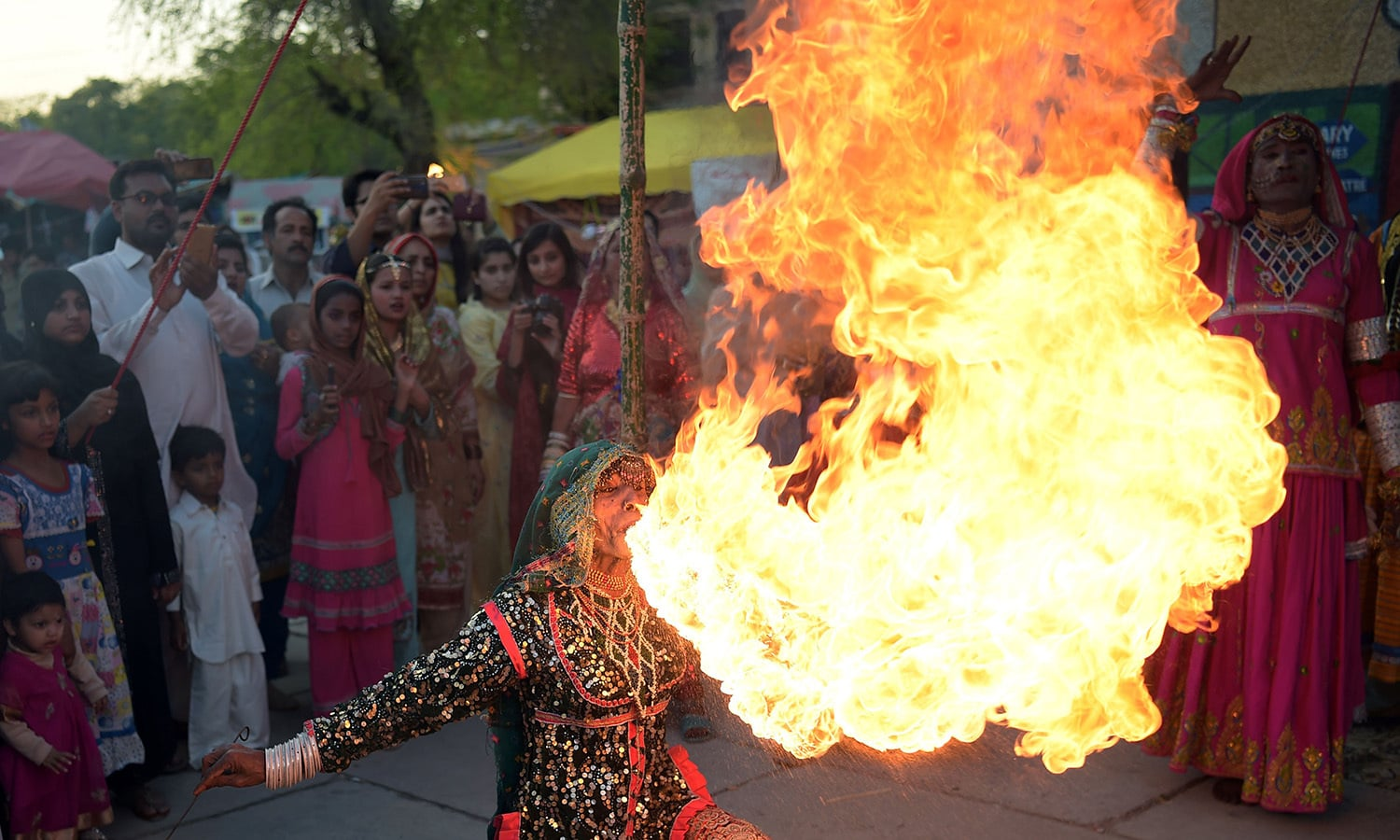 A Pakistani folk artist from Cholistan breathes fire as she performs during the annual Lok Mela festival ─ AFP