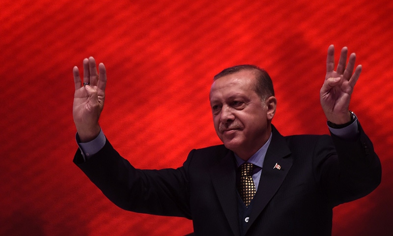 "Turkish President Recep Tayyip Erdogan flashes the four-finger ""rabia sign"" on April 12,  during a 15 July Martyrs meeting and a campaign rally for the ""yes"" vote in a constitutional referendum in Istanbul. ─ AFP"