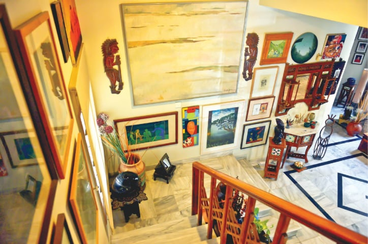 Looking down the stairs: a large landscape by Indian artist Neepa, with smaller landscape by Akram Dost Baloch, a small print by Naiza Khan, a miniature by Waseem Ahmad, and an early work by A.R. Nagori. -Photos by Fahim Siddiqi / White Star