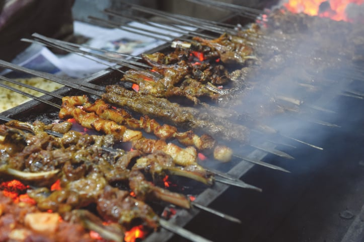 A row of skewers cook a variety of meats, from cubes of chicken to minced mutton