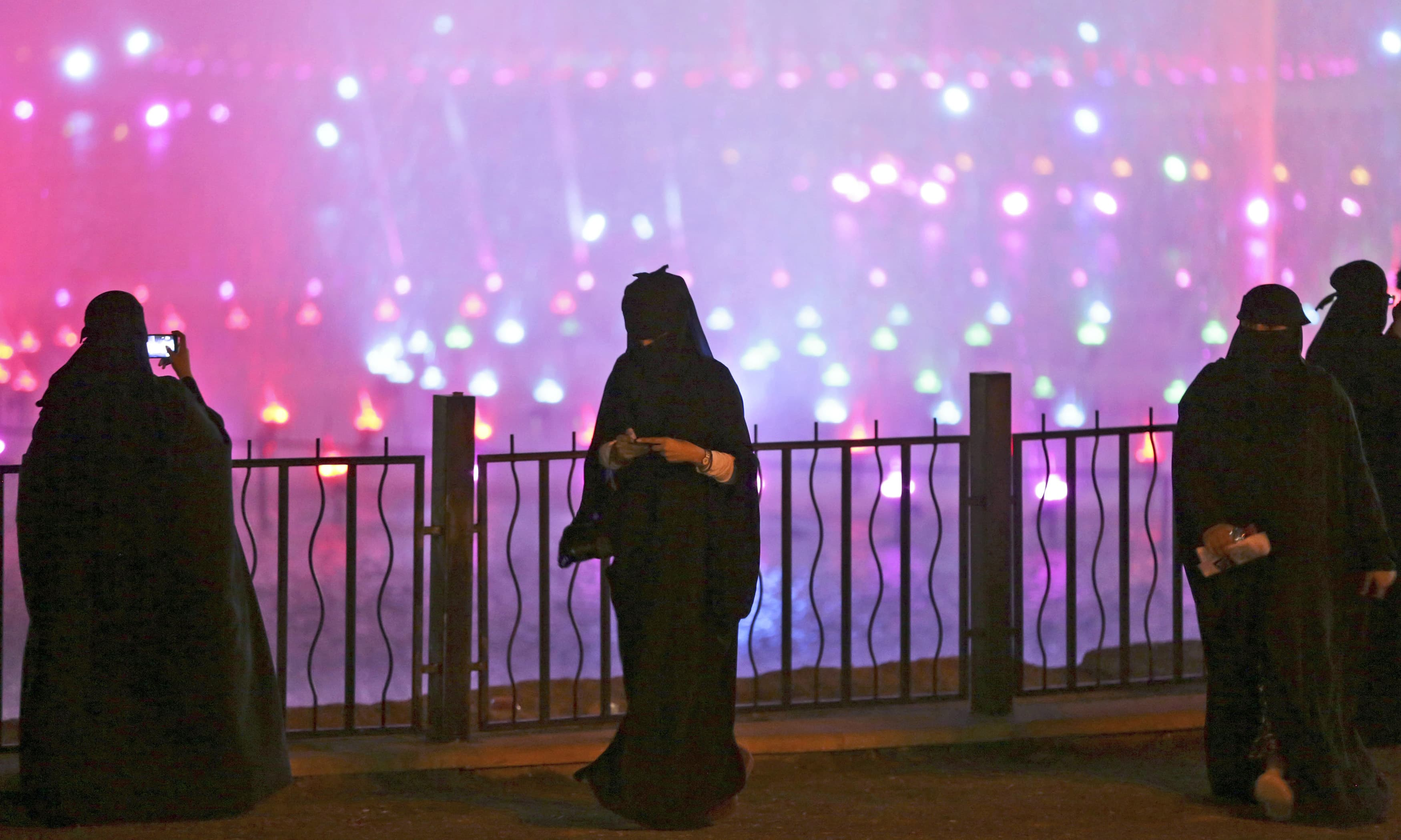 A Saudi woman takes photographs during celebrations to mark the Earth Hour in Riyadh. —AP/File