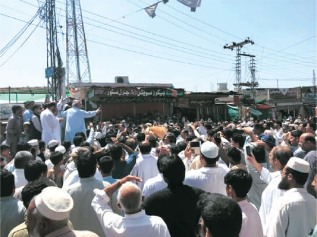 Protesters gather at a bazaar in Swabi on Sunday. — Dawn