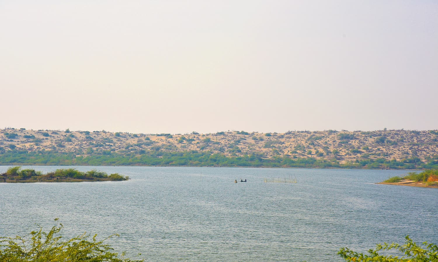 A view of the lake with sand dunes in the background.