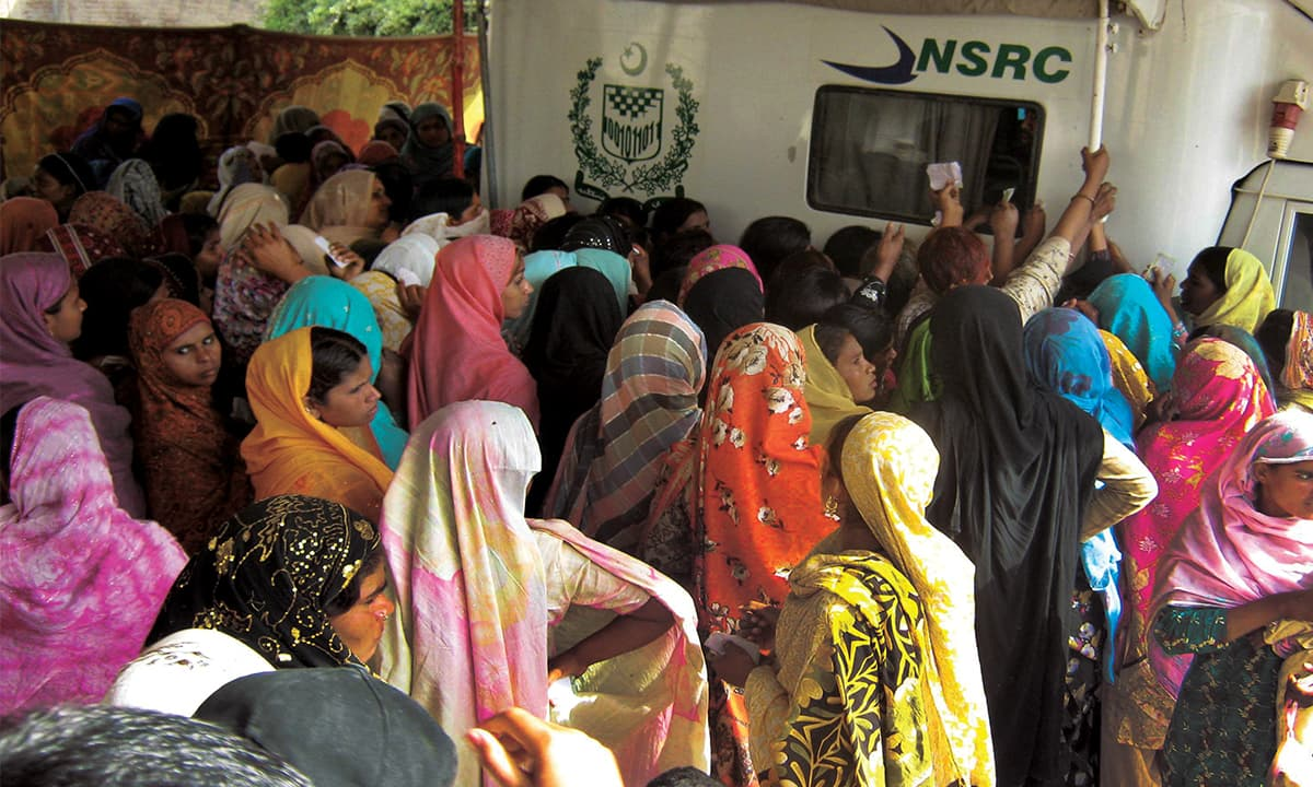 Women wait outside the Nadra's National Swift Registration Centre in Sahiwal | White Star