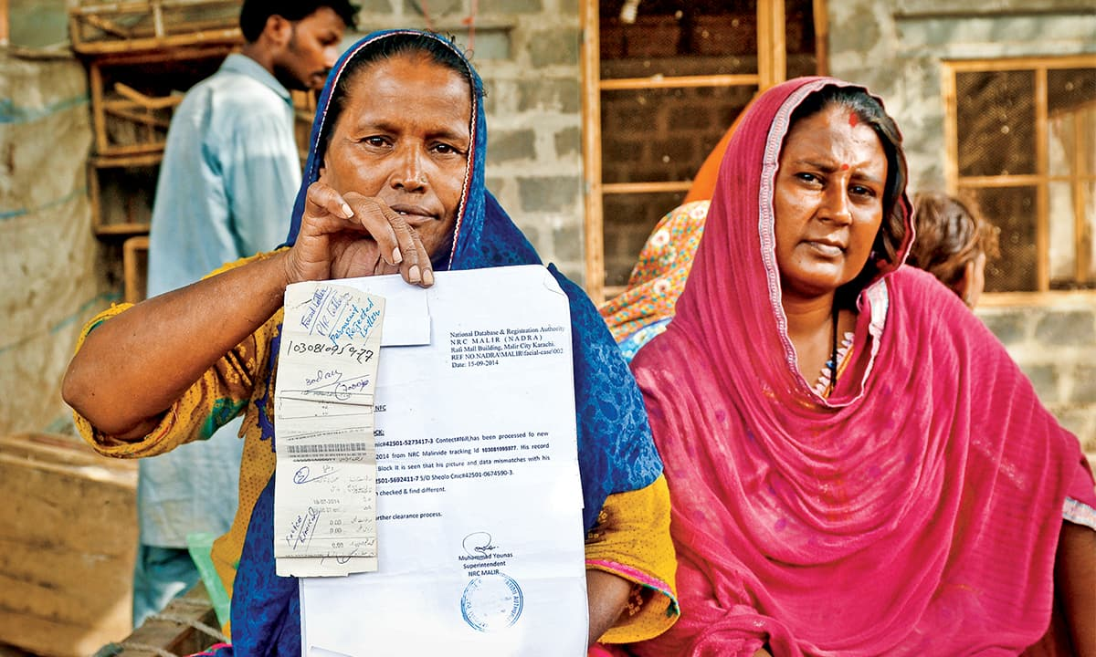 A woman holds up a CNIC application that was rejected by NADRA in Karachi | Fahim Siddiqui, White Star