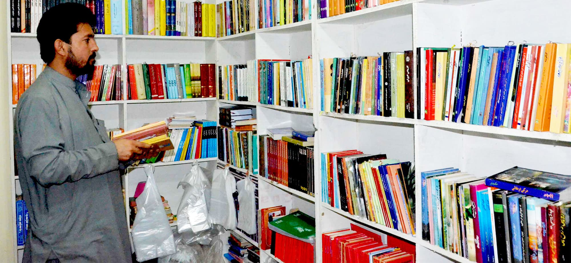 Baz Khan Alamyar overlooking his inventory of books, ranging from current affairs to philosophy
