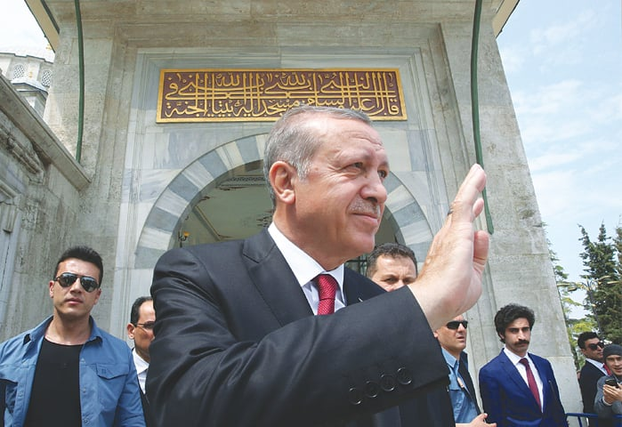 ISTANBUL: Recep Tayyip Erdogan greeting his supporters during a visit to Sultan Mehmet's tomb on Monday.—AFP