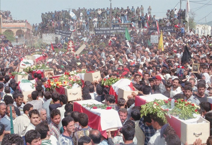 Mourners carry coffins draped in Lebanese flags as they arrive in the southern Lebanese village of Qana on April 30, 1996, to bury victims in a mass grave beside the UN post in which they were killed by Israeli shells.