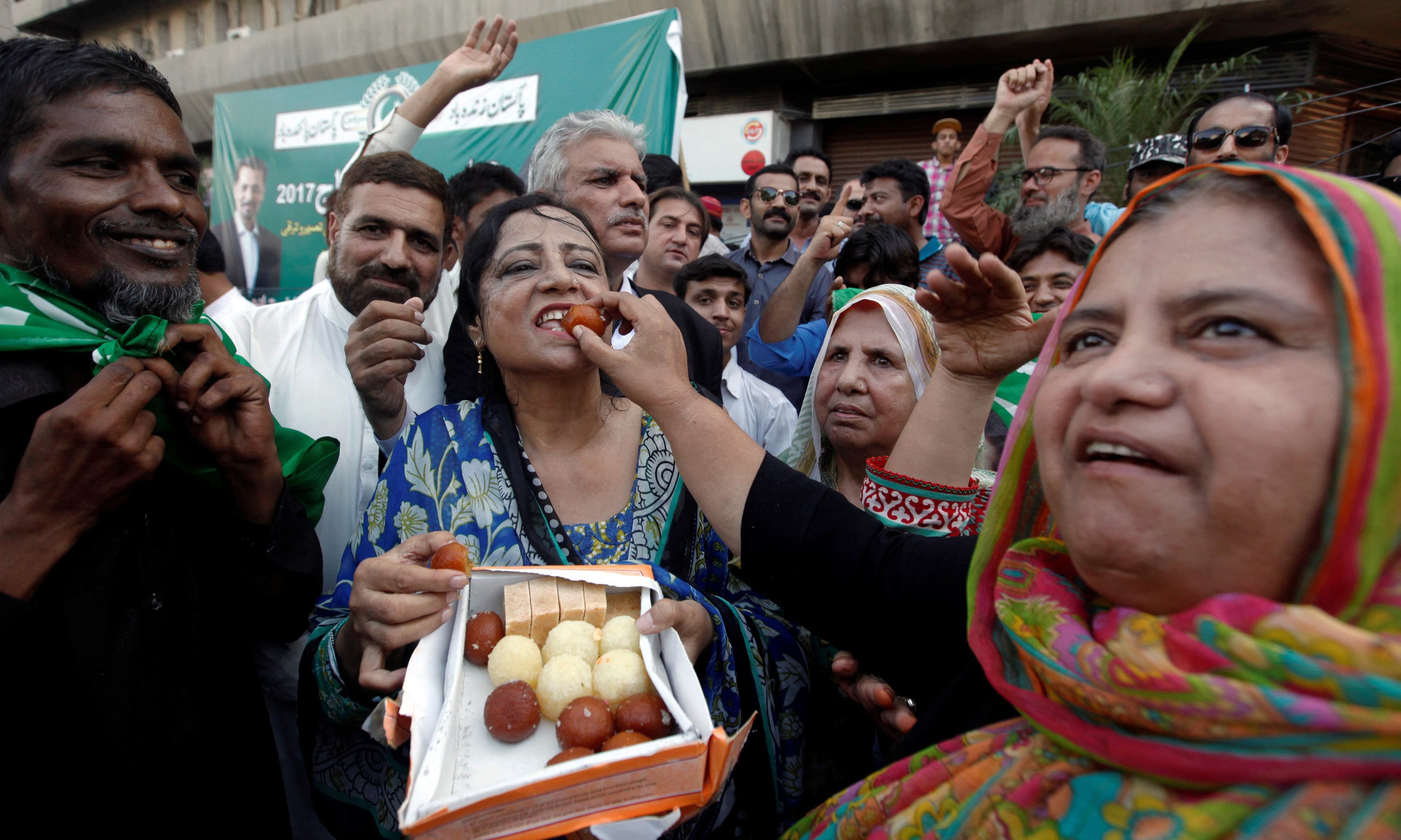 Supporters of PM Nawaz Sharif distribute sweets following Supreme Court's decision. ─Reuters