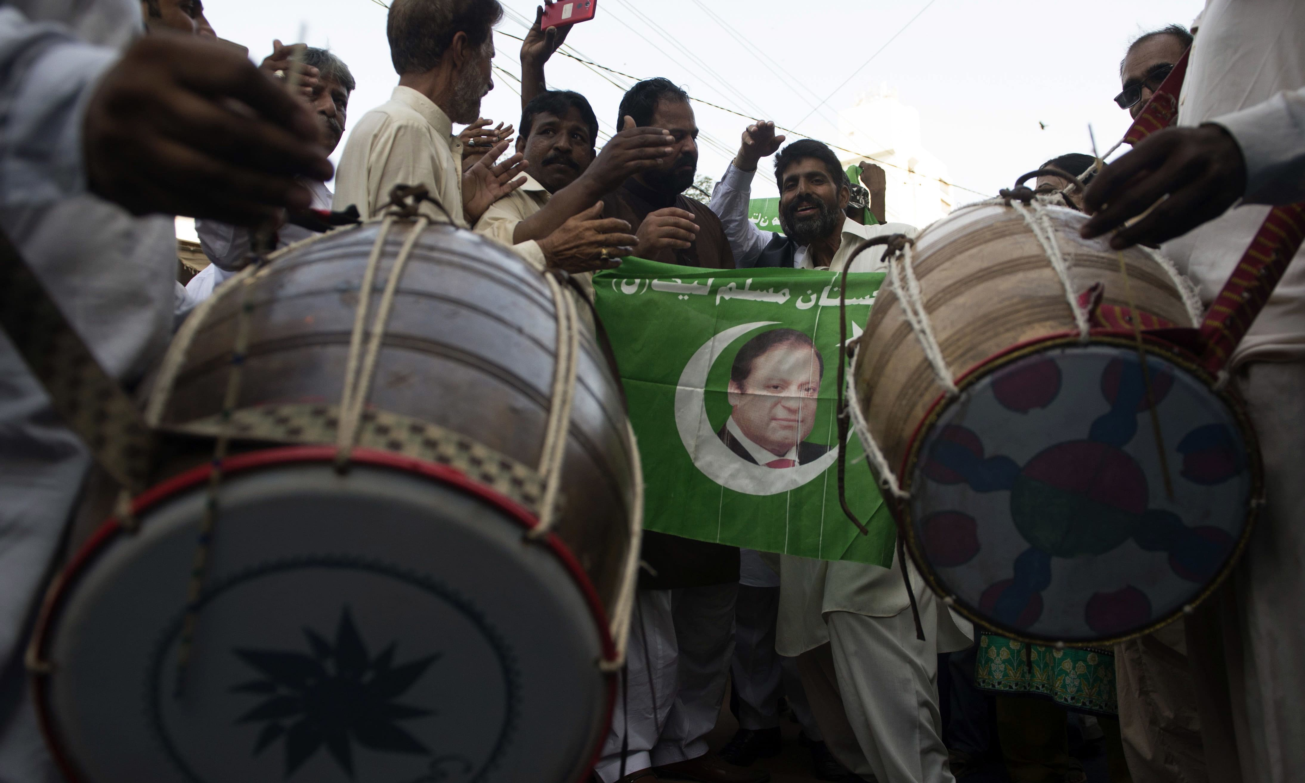 PML-N workers dance after the Supreme Court verdict.─AFP