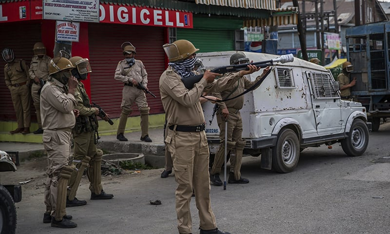 Indian policemen prepare to fire pellet guns on Kashmiri protesters. -AP