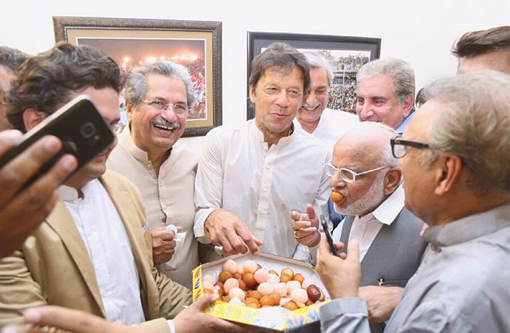 PTI chief Imran Khan along with his aides helps himself to some mithai at his Banigala residence after the announcement of the SC verdict on Thursday.—INP