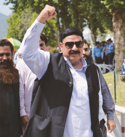 Awami Muslim League's Sheikh Rashid (left) punches his fist in the air as he arrives at the Supreme Court to listen to the judgement on the Panama Papers case on Thursday.—AFP/ White Star