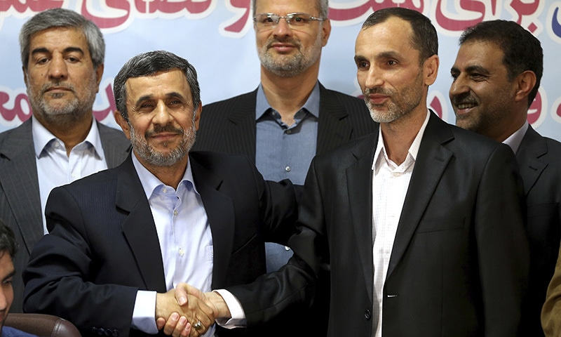 Ahmadinejad (left) and his close ally Hamid Baghaei, right, shake hands after registering their candidacy for the upcoming presidential elections on April 12. ─ AP