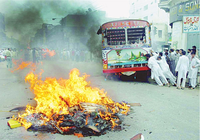 Another mob in Karachi trying to tip a bus over after it hit some schoolboys back in 2004. ─ White Star/File