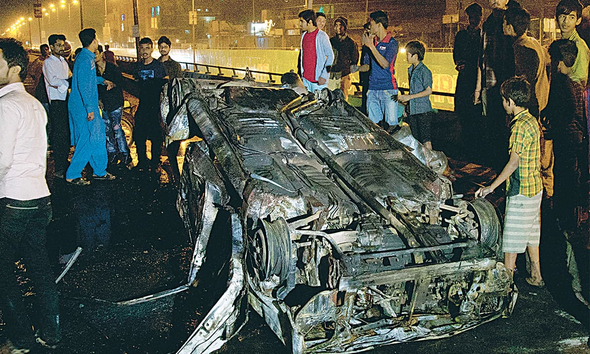 Onlookers surround the charred remains of a car set on fire in Liaquatabad, Karachi | White Star