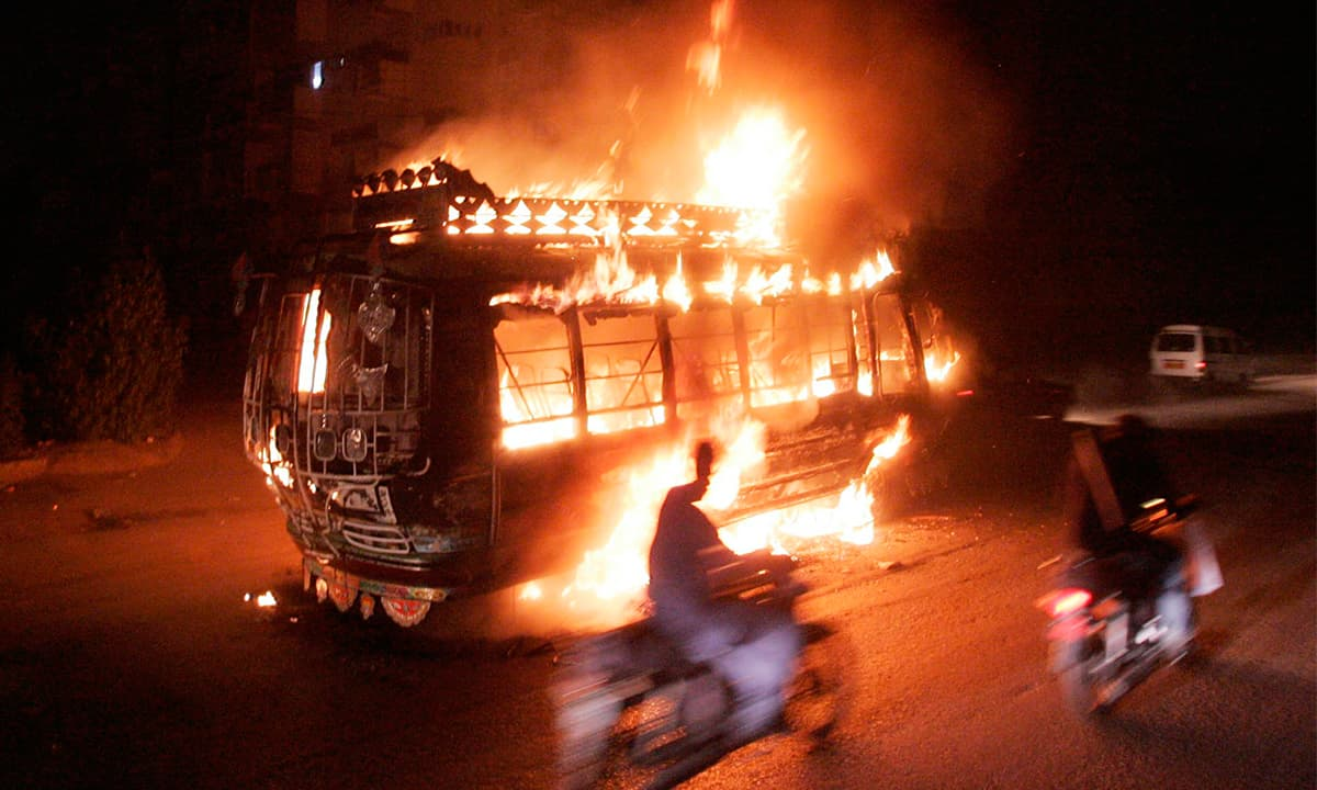 A bus burns on a street at night in Karachi | White Star