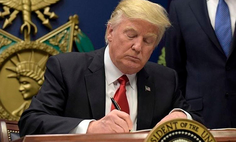 ڈونلڈ ٹرمپ امیگریشن ایگزیکٹو آرڈر پر دستخط کرتے ہوئے —فائل فوٹو/ رائٹرز