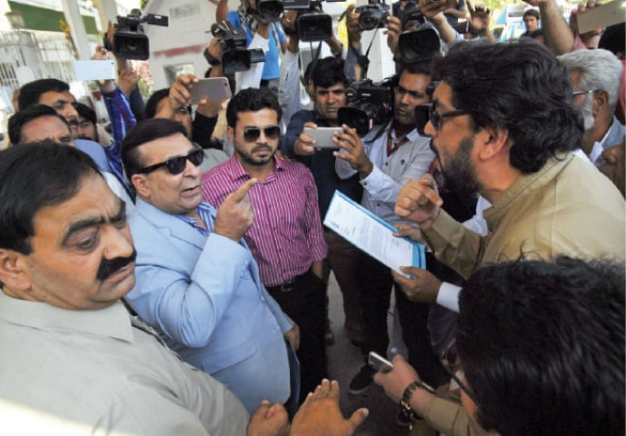 PTI MNA Sheheryar Afridi (right) faces off with government officials outside the Press Information Department premises on Thursday. — White Star