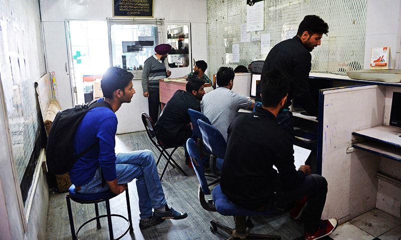 This photo shows Kashmiri men in an internet cafe in Srinagar.—AFP