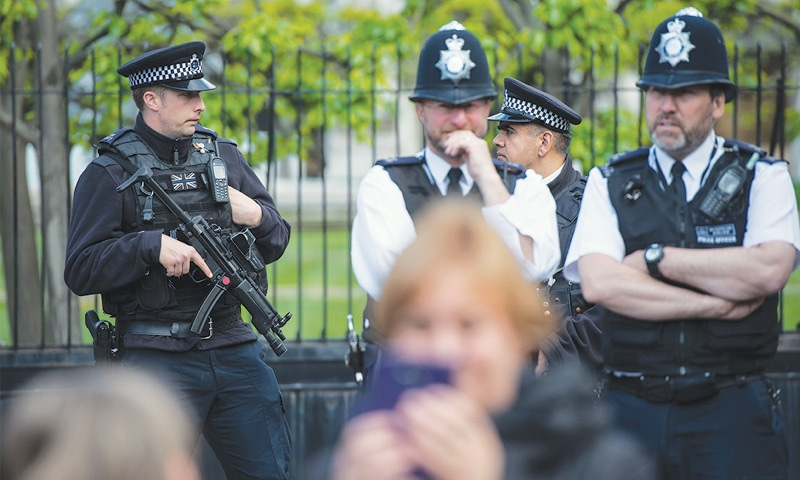 Tourists take photographs as armed police officers stand guard outside the Houses of Parliament on Friday.—AFP