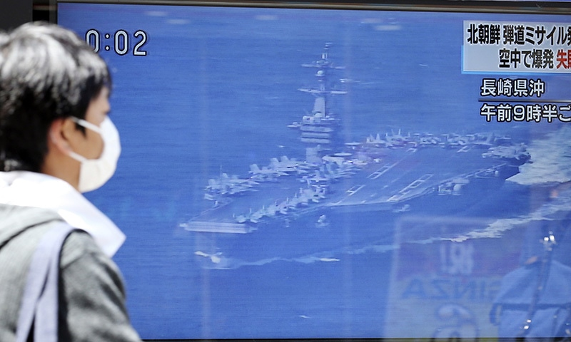 A man walks past a TV news showing an image of USS aircraft carrier Carl Vinson while reporting North Korea's missile test, in Tokyo, Saturday, April 29.— AP