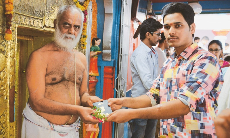 Hyderabad (Telangana, India): A devotee (right) receives his passport after it is blessed by a priest at the Chilkur Balaji Temple on Saturday.—AFP