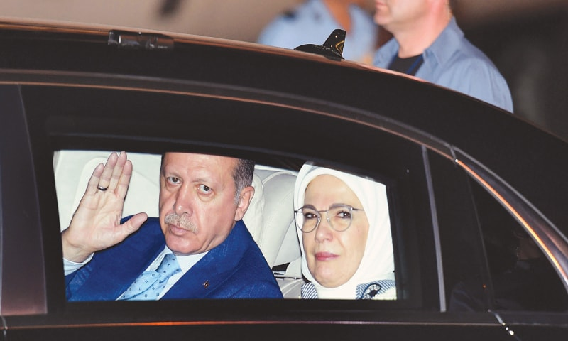 Turkey's President Recep Tayyip Erdogan waves, with his wife Emine seated beside him, as they leave the airport upon arrival in New Delhi, India, Sunday.— AP