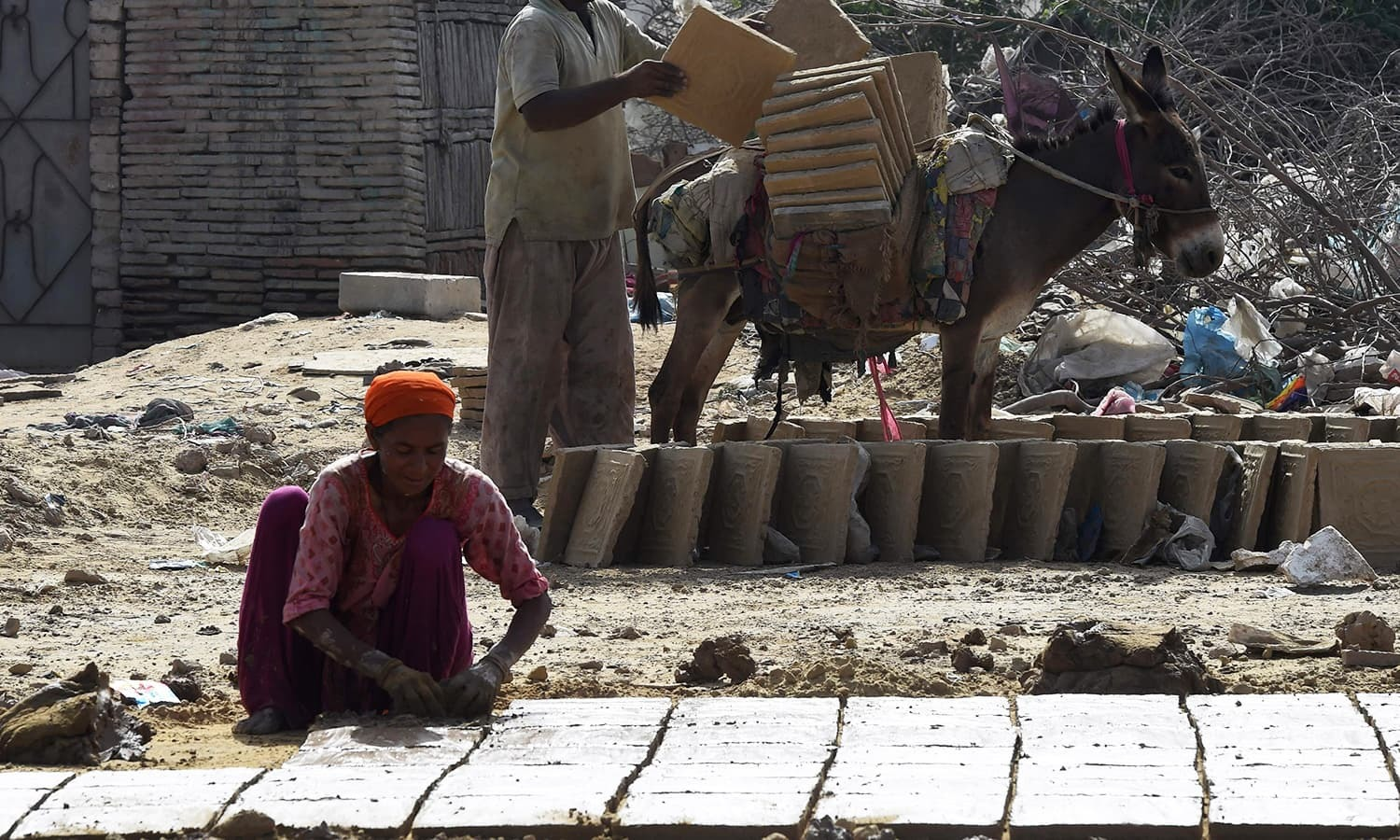 Labourers make bricks at a factory in Karachi. -AFP