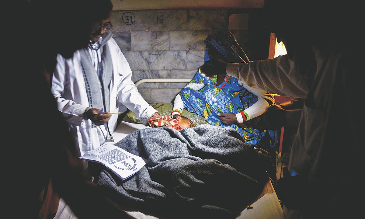 A doctor checks the thermometre reading of a patient during a poer outage at Mithi Civil Hospital in Tharparkar | Fahim Siddiqui, White Star