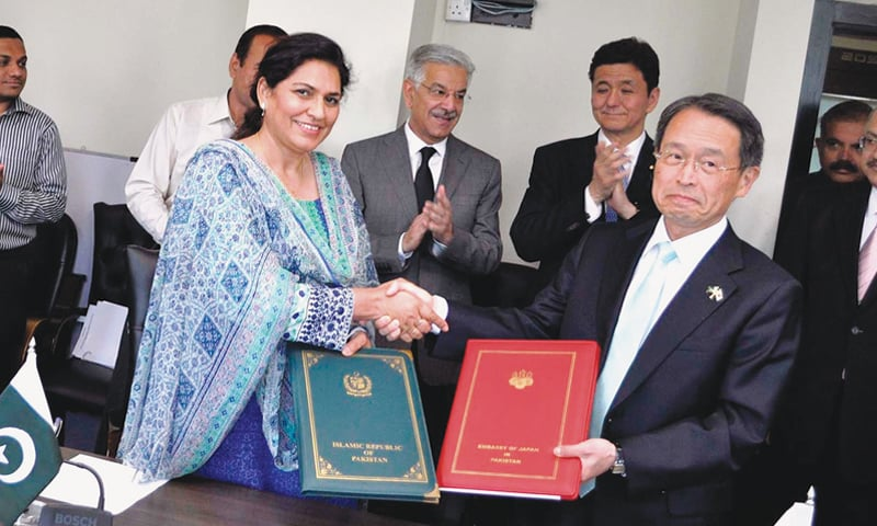 The Japanese ambassador to Pakistan, Takashi Kurai, and Anjum Assad Amin, the additional secretary of the economic affairs division, exchanging documents after signing an agreement at the water and power ministry.—APP