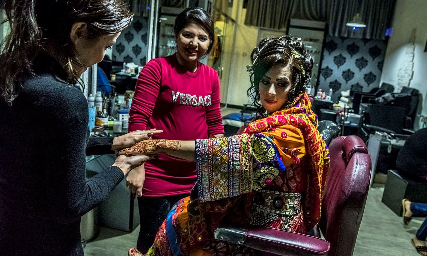 An Afghan bride dressed in a traditional wedding gown sits as a beautician applies moisturiser ahead of her wedding party at a beauty parlour in Kabul. — AFP