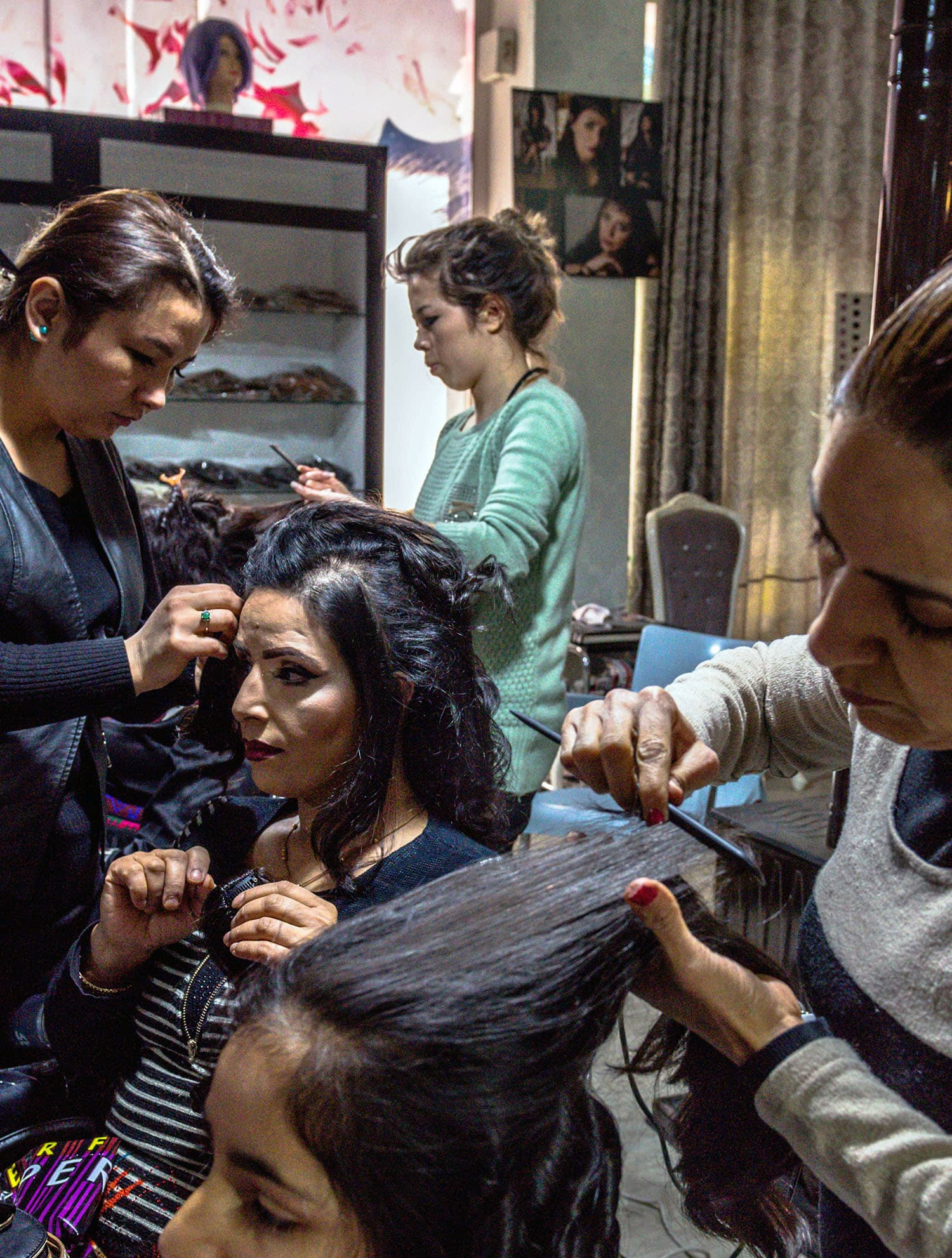 Afghan clients sit while their hair is styled at a beauty parlour in Kabul. ─AFP